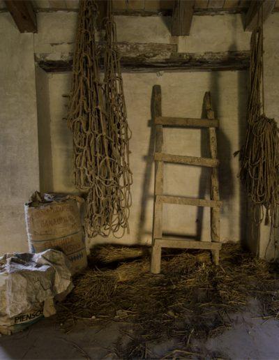 Estat de l'antiga pallissa situada a l'edifici annex al molí Descals. Al bell mig de la fotografia es poden vorer penjats de les bigues de fusta dos aixabegons, antigues malles fetes amb cordes que s'empraven per a encabir la palla i poder traslladar-la o simplement emmagatzemar-la.