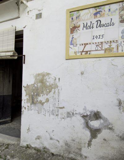 """Entrada a l'edifici on hi ha el molí i la casa del fariner. A la paret dreta, segons s'entra, hi ha una rajols de ceràmica coneguts popularment com """"manises"""" amb diferents motius que assenyalen les parts del molí i les feines relacionades amb ell. Allò més destacat, però, és la data de 1415, any en què apareix documentat per primera vegada . Al llindar de la porta hi ha, partida en dues parts, una de les moles que ha utilitzat el molí."""