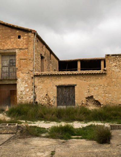 Vista frontal de la casa. Amb l'oratori a la dreta i la casa a l'esquerra. Entre els dos s'endevina el pati que els separa. L'estat de runa és evident en la part alta de l'habitatge on el sostre s'ensorra i en els esvorancs que comencen a clapejar els murs de la casa.